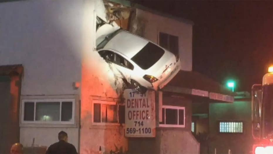 Car launches off curb, crashes into second floor of building