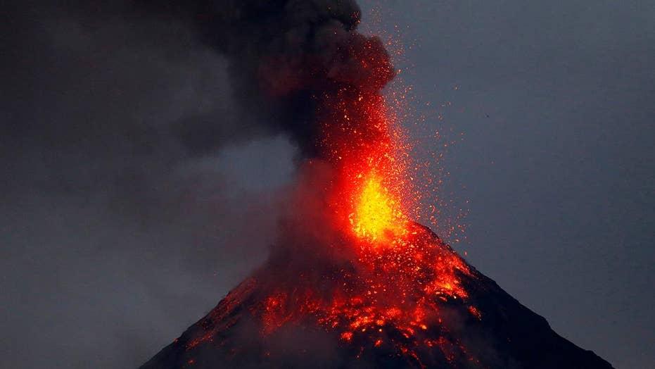 Erupting volcano lights up night sky in Philippines