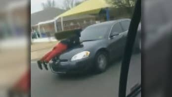 Raw video: Man holds on to car hood as vehicle travels down busy stretch of road in Tennessee.