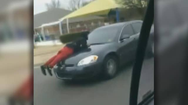 Man clings to car as driver speeds down busy street