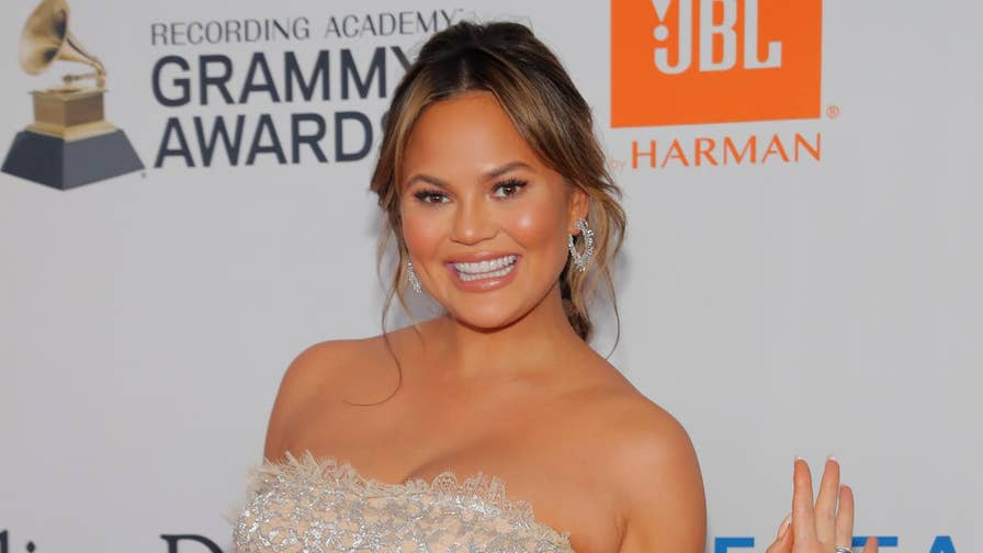 Fox411: Chrissy Teigen shows off her pregnant belly in a topless, salad-making Instagram photo.