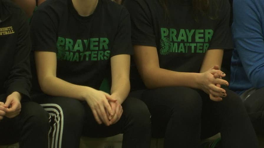 "Parents sported ""Prayer Matters"" shirts in a silent protest against the ban"