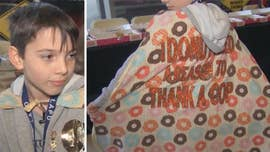 "Like his cape says, this 9-year-old boy ""donut need a reason to thank a cop."""