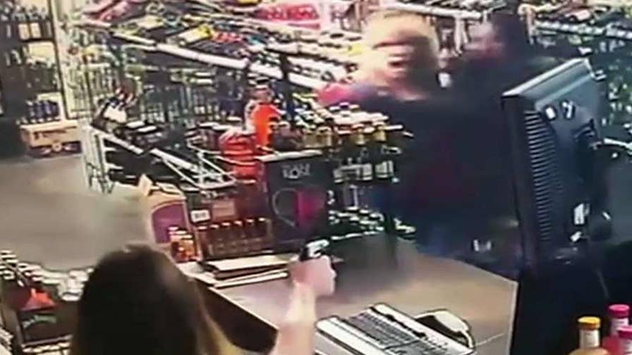Video shows a woman shooting at an armed robbery suspect in an Oklahoma liquor store.