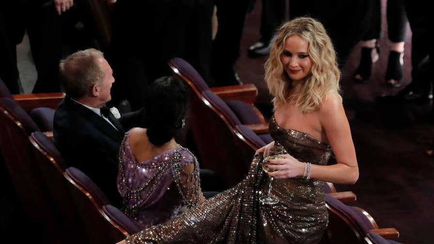 In true Jennifer Lawrence fashion the 27-year-old was caught juggling a glass of white wine while stepping over a seat in the theater. You have to see it.
