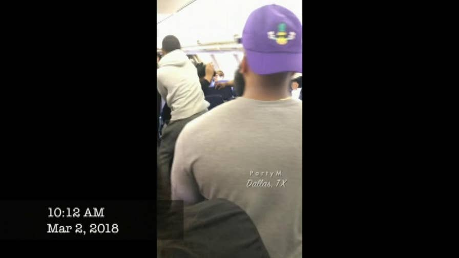 After arguing with flight attendants over bin space, two passengers threw down in a brutal fist fight. The brouhaha delayed the Dallas to Los Angeles flight by an hour. You have to see this video.