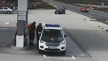 Raw video: Surveillance camera captures extremely close call when vehicle swerves to avoid another car and narrowly misses gas station attendant, police officer in Monovar, Spain.