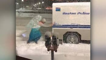 Raw video: Onlookers watch with delight as man dressed as 'Frozen' character pushes Boston police vehicle from snowbank.