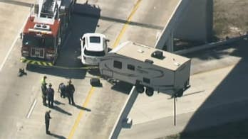 Raw video: RV trailer's back wheels hang over guard rail after crash on Interstate 275 in St. Petersburg, Florida.