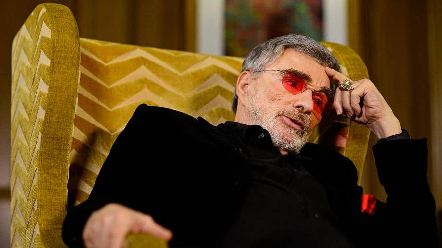 """During an interview with """"Today's"""" Hoda Kotb, legendary actor Burt Reynolds made some strange comments about Kotb's lips and Sally Field. Now the Hollywood icon clarified his bizarre remarks."""