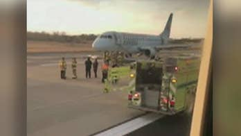 Emergency crews meet Air Canada plane on tarmac after flight from Toronto was forced to make emergency landing at Dulles International Airport.