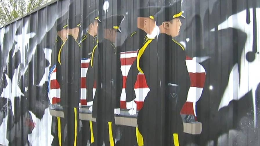 Mural honoring officers killed in ambush removed due to city code violations.