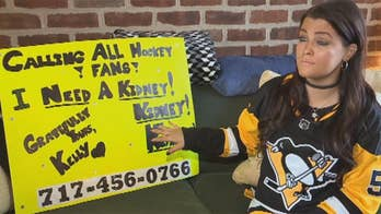 Thirty year-old Kelly Sowatsky brings neon poster with plea for a kindey donor to Pittsburgh Penguins game.