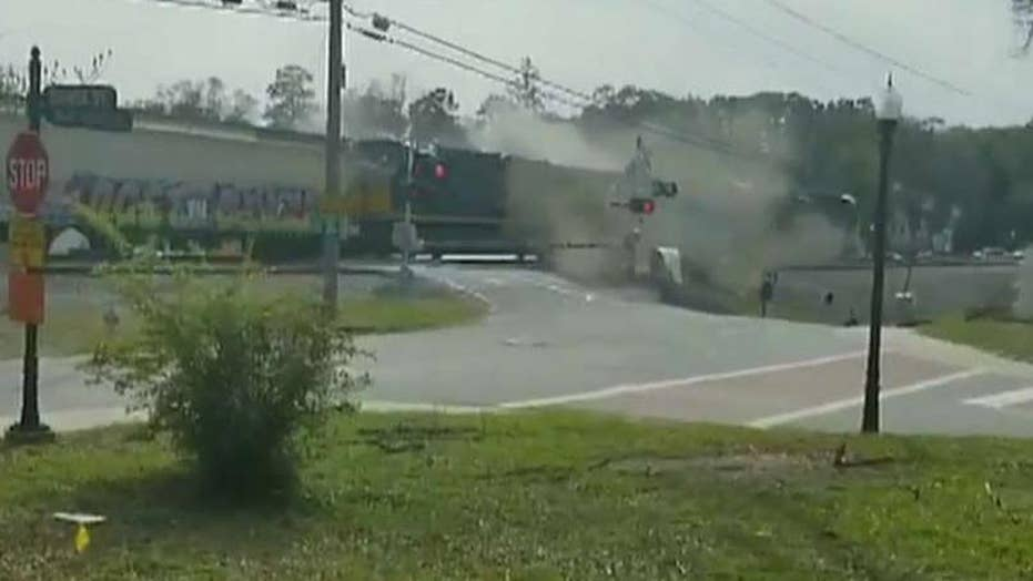 Freight train plows through tractor trailer stuck on tracks