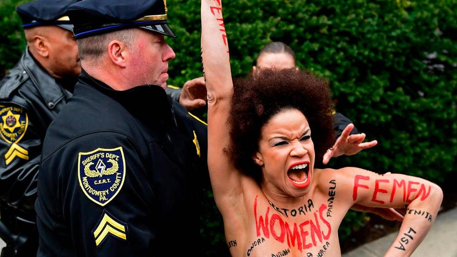 Raw video: Chanting 'women's lives matter,' an unidentified female protester is tackled by police as she attempts to intercept Bill Cosby as he arrived at a courthouse in Pennsylvania.
