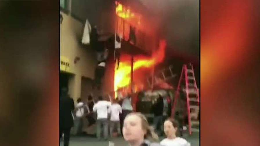 Dramatic escape caught on camera as flames rip through dance studio in New Jersey.