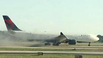 Raw video: Smoke pours from Delta plane after an emergency landing in Atlanta.