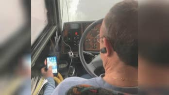 Passenger captures bus driver watching videos while driving on the freeway.