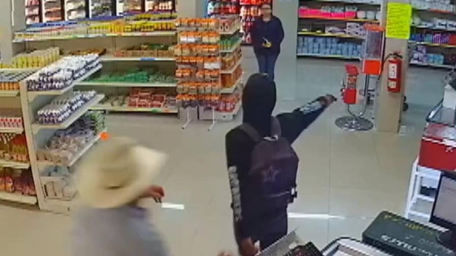 Surveillance video captures man in cowboy hat disarming the pistol-brandishing suspect in a butcher shop in Monterrey.
