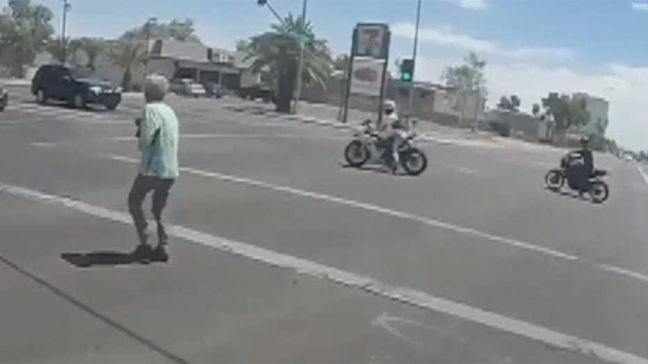 Motorcyclists stop traffic to help woman cross street