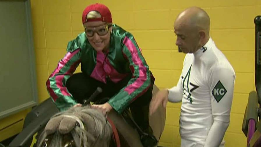Fox News meteorologist Janice Dean gets a lesson on how to ride a horse during a race while she attends the Kentucky Derby.