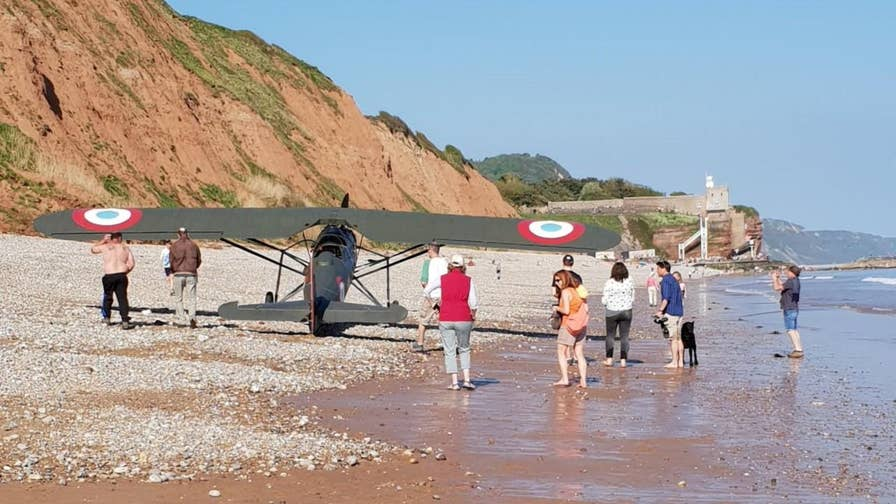 A WWI-era plane near the southern coast of England was forced to make an emergency landing on a beach full of onlookers.