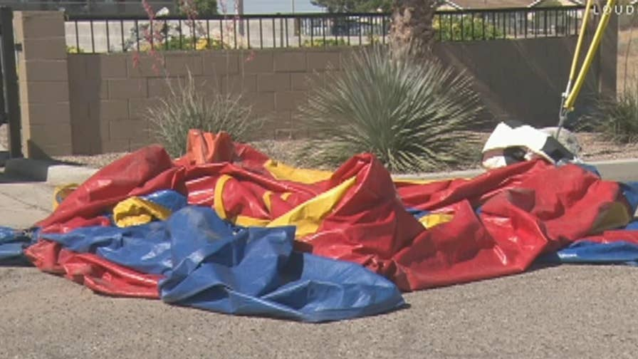 The 9-year-old fell out of the bounce house as it rolled onto the highway; he was taken to the hospital for minor injuries.