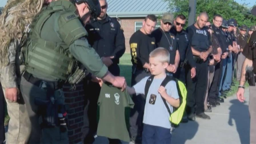 Indiana 5-year-old whose father was killed in the line of duty returns to school with the support of Terre Haute police officers.