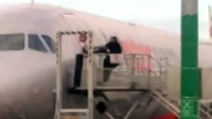 Must-see video shows a Melbourne man trying to pry open a locked airplane door after he missed his flight. He allegedly stormed the gate, pushed past the crew and ran to plane.