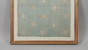 See an iconic flag that demarcated George Washington's presence on the battlefield during the Revolutionary War. Why do the stars on it look the way they do and where is the flag being displayed?