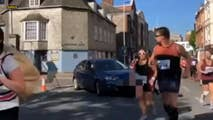 A driver in Plymouth, U.K, took a dangerous turn when she slowly pulled her car thorough a barrier of traffic cones and into the path of the runners taking part in a half marathon passing through her town.