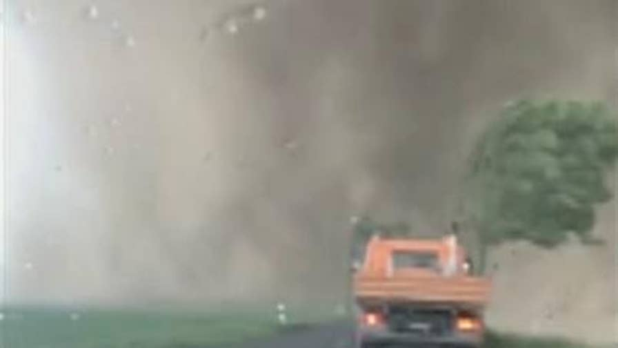 Motorists come dangerously close to a funnel cloud when a powerful storm ripped through the Lower Rhine region of Germany.