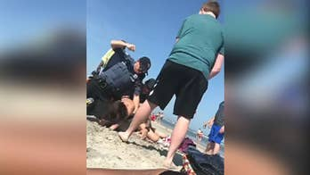 A Twitter video shows police officers wrestling a woman to the ground and punching her in the head at Wildwood beach.