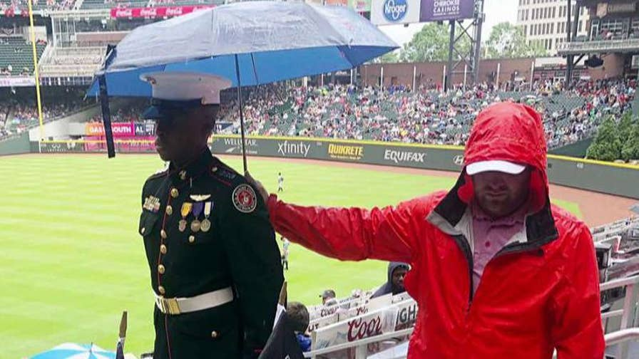 Baseball fan holds an umbrella over a JROTC cadet to shield him from the rain during a Braves game.