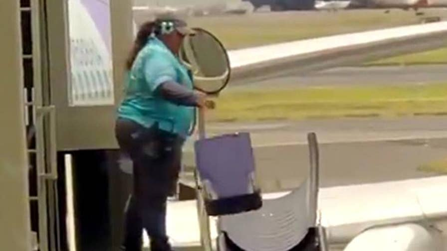 Viral video of a Hawaiian Airlines baggage handler tossing suitcases down a metal shoot sparks a debate on Twitter.