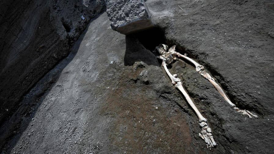 Archaeologists have uncovered the skeleton of a man crushed by 660-pound stone during the eruption of Mount Vesuvius.