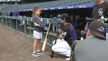 Nevada girl, 8, with robotic hand throws first pitch at Colorado Rockies game