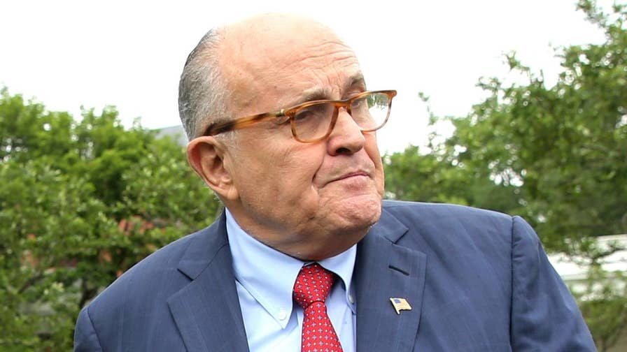 Rudy Giuliani answers questions from reporters while attending an event on the White House lawn.