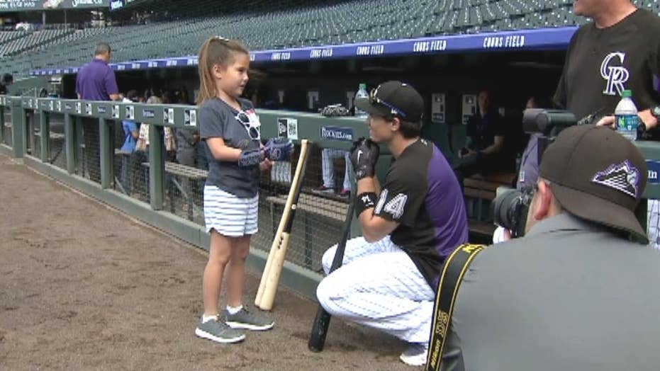 Girl with robotic hand throws out first pitch at baseball game
