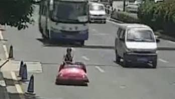 Raw video: Chinese police officers stop woman riding down busy street in bumper car and seize the mini-vehicle.