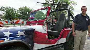 Gubernatorial candidate shocks parade-goers with replica gun mounted on Jeep.