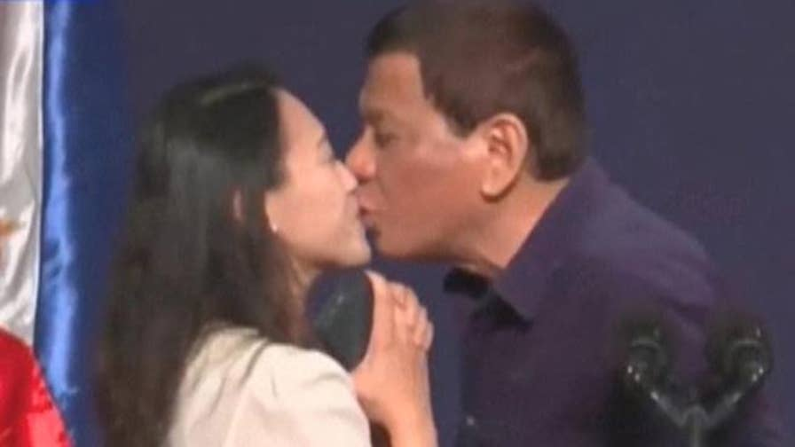 Philippine President Rodrigo Duterte kisses a woman he called up on stage during a meeting with thousands of Filipino workers in Seoul.