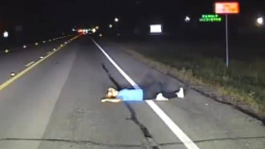 Police dashcam video shows a woman found sleeping on a road in Fulshear, Texas, narrowly escaping being hit by a vehicle.