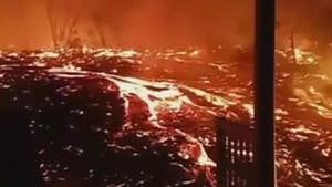 A man films from the second story of his house as lava creeps closer.
