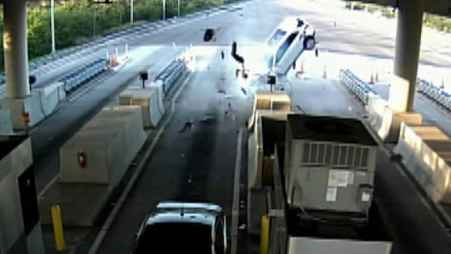 Raw video shows passenger being expelled through car windshield after slamming into a toll booth divider.