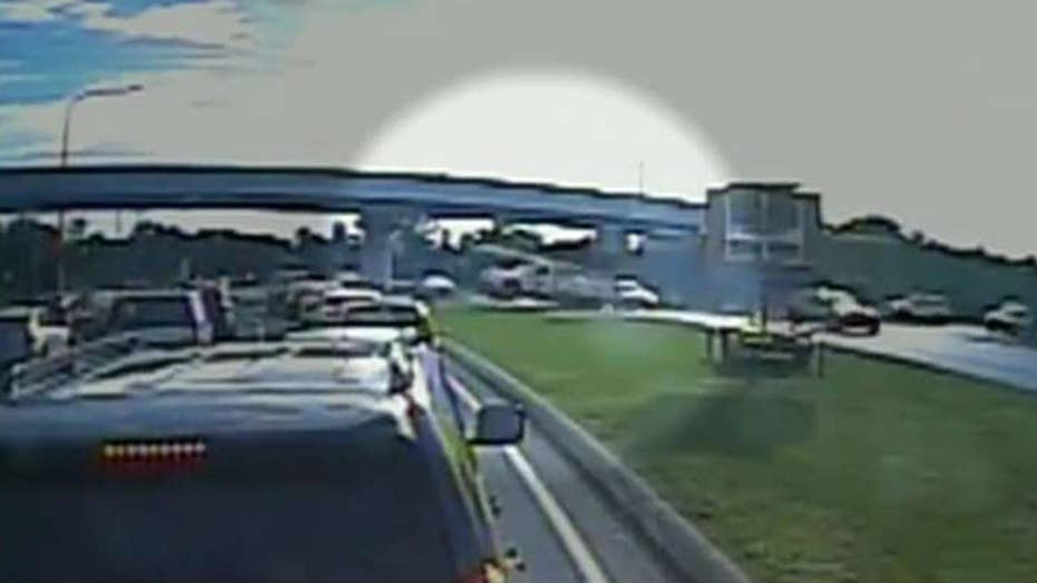 Truck goes airborne across highway, lands on 3 cars