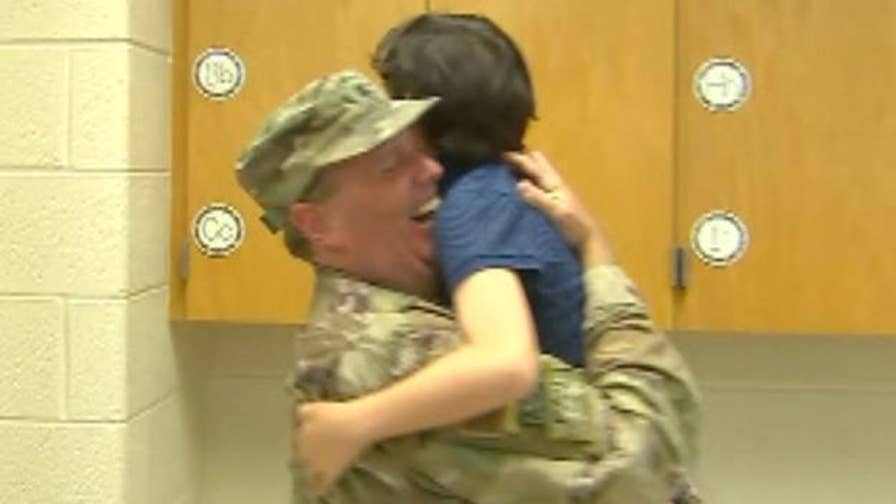 U.S. Navy Reserve commander surprises his son in tearful reunion at Arlington school after returning from deployment.