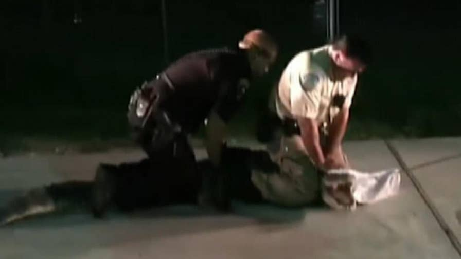 Raw video: Aransas Pass Police Department officers control 8-foot reptile that tried to sneak out of a pond and wander through parking lot.