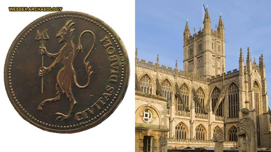 Workers on a renovation project at Bath Abbey in the U.K. made a startling discovery when they removed seating in the ancient church - a pair of mysterious coins depicting a devil were beneath the row of seats.