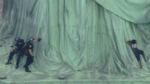 The woman climbed to the statue's base from the pedestal.